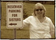 Blonde woman beside reserved parking for sisters sign